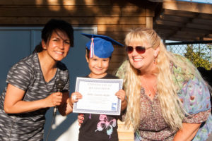 Child with his teachers at Early Learning graduation ceremony