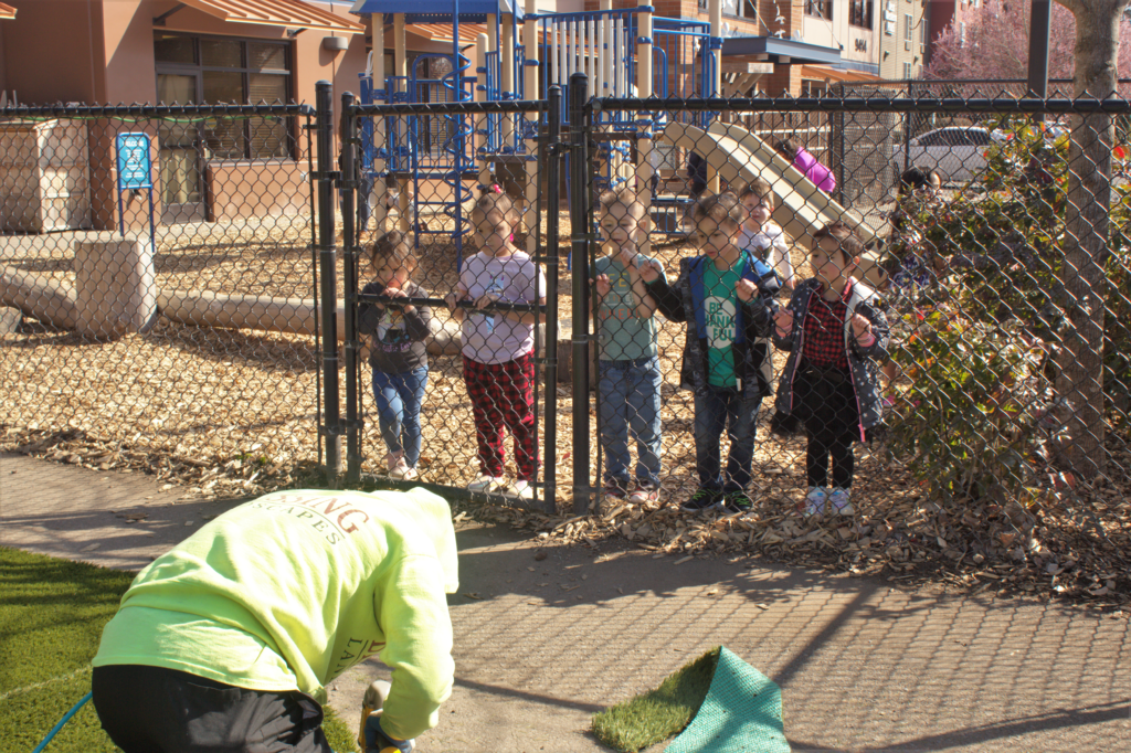 Early Learning children looking on the landscaper through a chain-link fence.